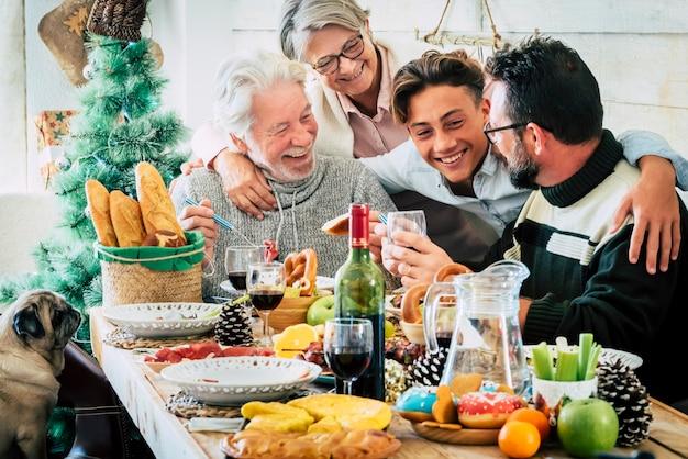 Familie van drie generaties die samen dineren op de eettafel terwijl ze kerst thuis vieren