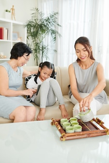 Familie van drie generaties die tijd samen thuis doorbrengt, thee drinkt en spelletjes speelt op digitale tablet