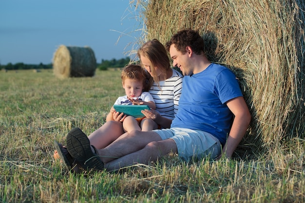 Familie van drie met een pad in het veld met hooibroodjes