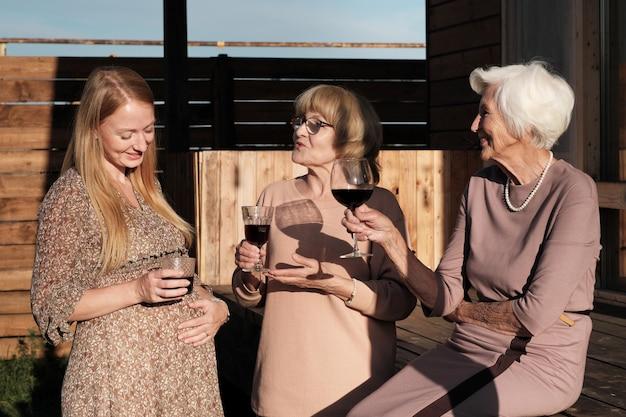 Familie van drie staande buiten praten met elkaar drinken van rode wijn ze rusten op frisse lucht