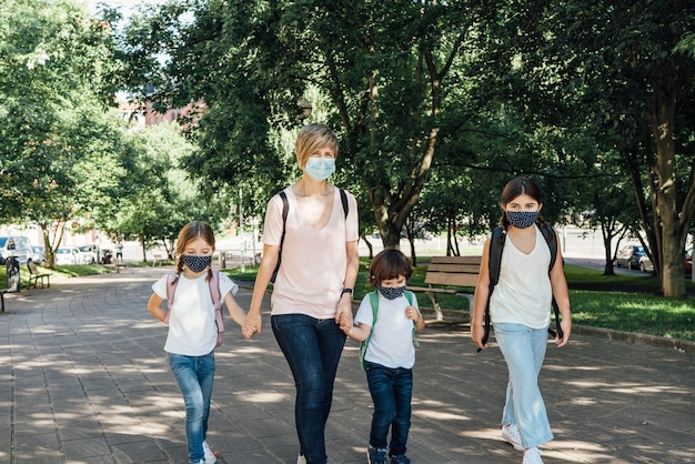 Familie van een moeder met haar drie blanke kinderen die aan het begin van het schooljaar naar school gaan en maskers dragen vanwege de coronaviruspandemie covid19