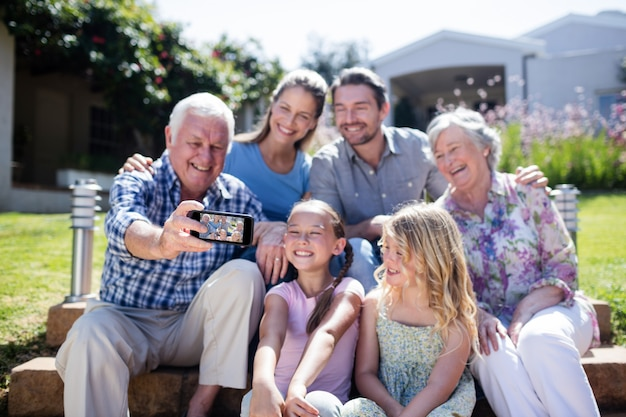 Familie van meerdere generaties die een selfie in de tuin nemen