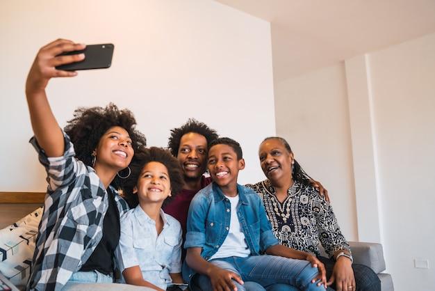 Familie van meerdere generaties die selfie met telefoon thuis nemen.