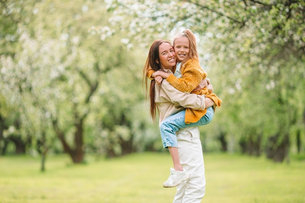 Familie van moeder en dochter in bloeiende kersentuin