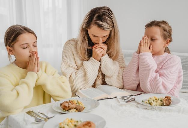 Familie van moeder en kinderen bidden aan tafel