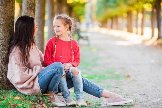 Familie van moeder en klein kind buiten in park bij herfstdag