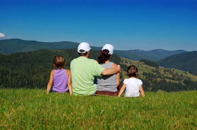 Familie van ouders en twee kinderen zitten op het gras en kijken naar het prachtige uitzicht op de bergen