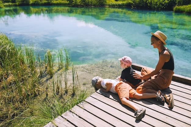 Familie van toeristen in de natuur jonge vrouw met kleine kinderen op houten brug in de groene natuur