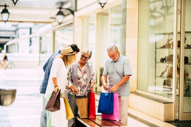 Familie van twee volwassenen en twee senioren samen in een winkelcentrum winkelen en cadeautjes en kleding kopen voor kerstmis - zoveel tassen in hun armen