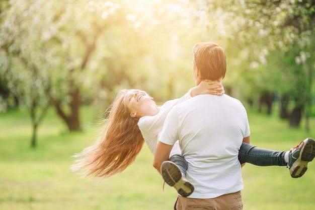 Familie van vader en dochter in bloeiende kersentuin