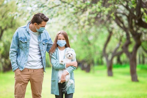 Familie van vader en dochtertje met puppy die beschermend medisch masker buiten in het park dragen