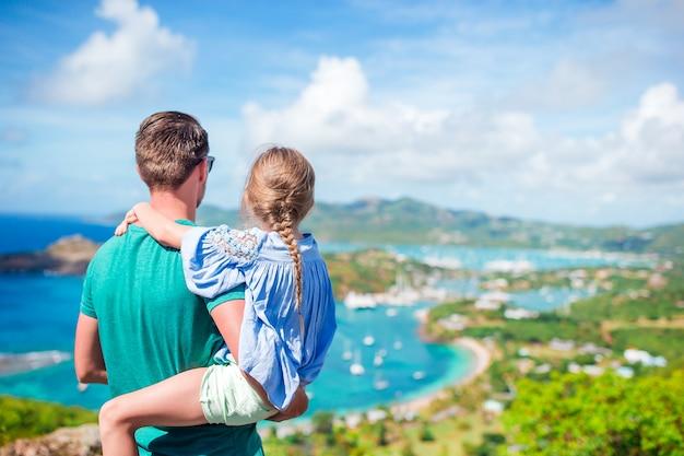 Familie van vader en klein kind genieten van het uitzicht op de schilderachtige engelse haven van antigua in de caribische zee