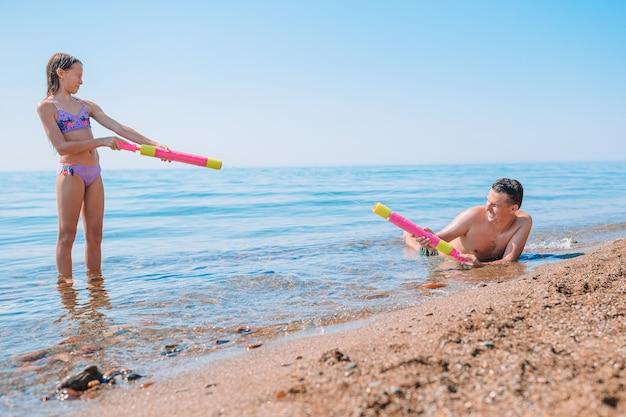 Familie van vader en zijn dochter plezier op het strand en spatten