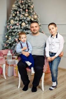 Familie van vader en zonen dichtbij kerstboom