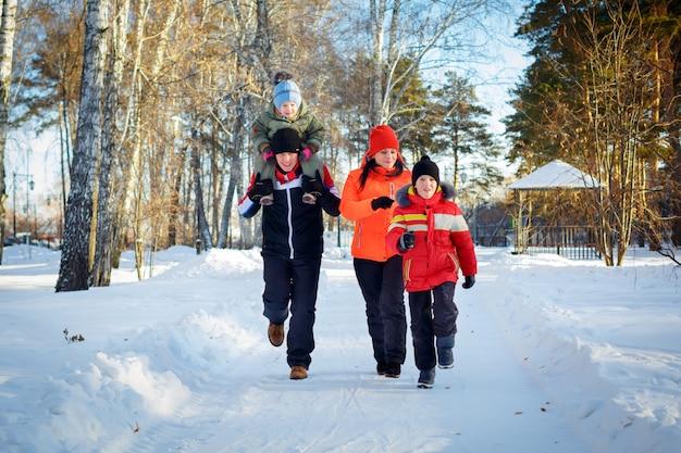 Familie van vier die in de winterpark genieten van