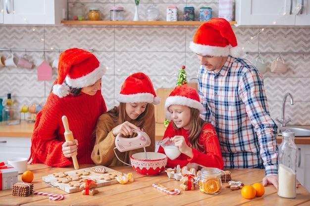 Familie van vier die koekjes voorbereiden voor kerstmis in de keuken. prettige kerstdagen en fijne feestdagen.