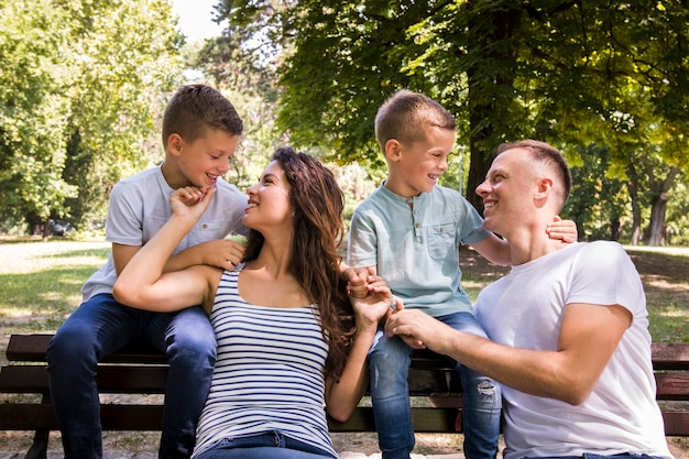 Familie van vier die op een bank rusten