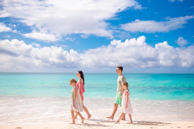 Familie van vier die op wit strand lopen