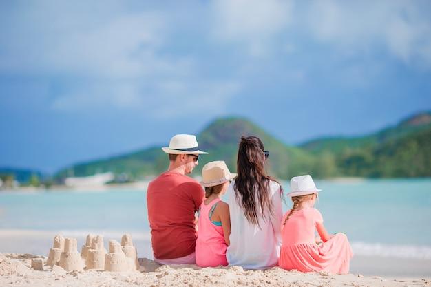 Familie van vier die zandkasteel maken bij tropica strand