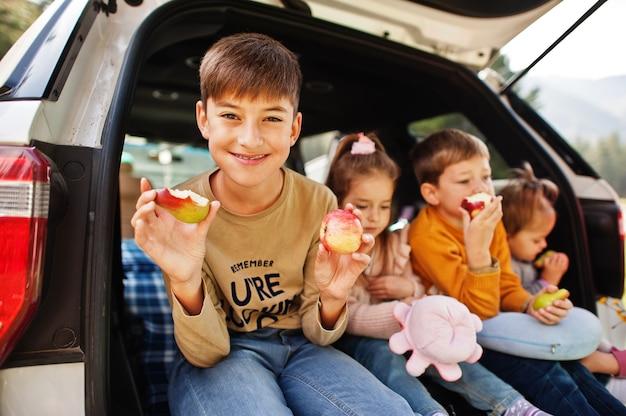 Familie van vier kinderen eet appels in het interieur van het voertuig. kinderen zitten in de kofferbak. reizen met de auto in de bergen, sfeerconcept.