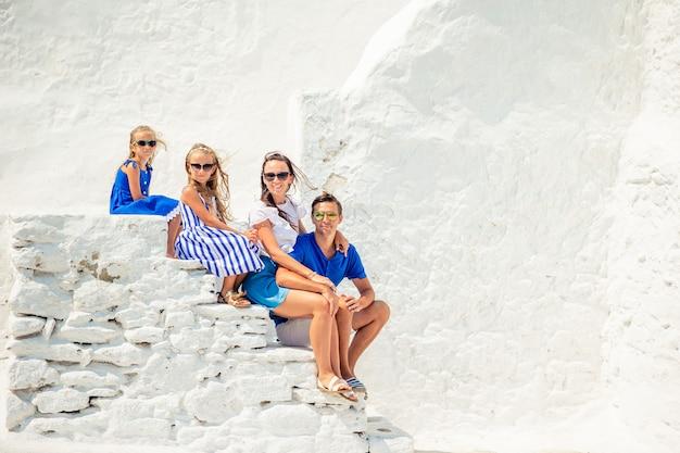 Familie van vier op de trappen van de paraportiani-kerk op mykonos