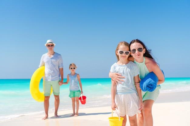 Familie van vier op een tropisch strand