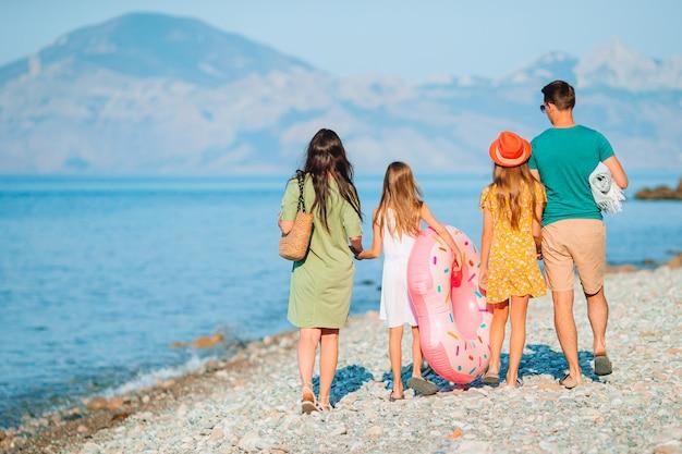 Familie van vier op het strand dat pret heeft. kinderen en ouders aan de kust gaan zwemmen