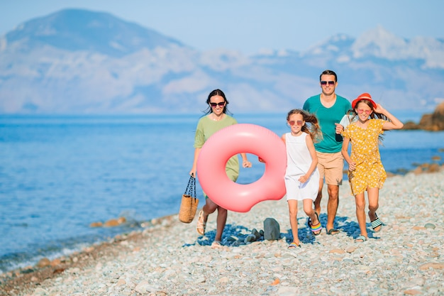 Familie van vier op het strand dat pret heeft. kinderen en ouders rennen aan de kust