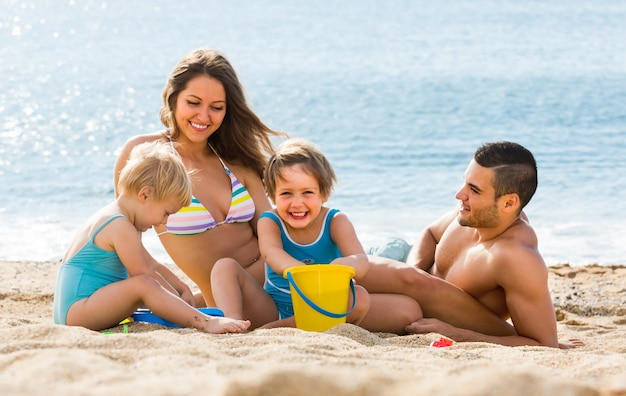 Familie van vier op het strand
