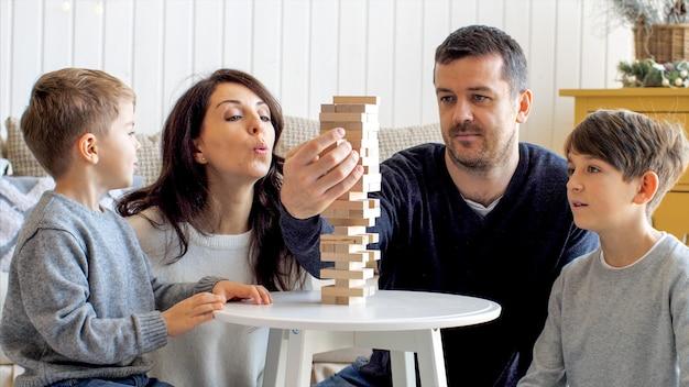 Familie van vier personen speelt thuis samen in bordspel met houten toren.