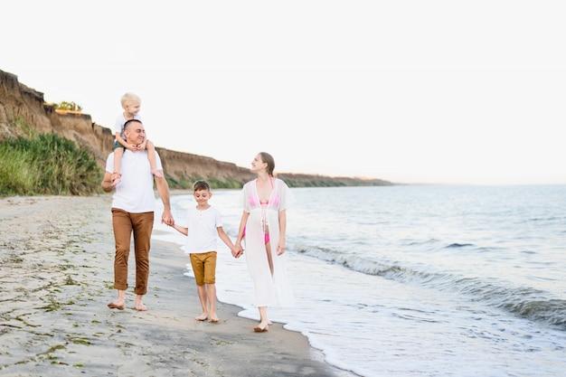 Familie van vier wandelen langs de kust. ouders en twee zonen. gelukkig vriendelijke familie