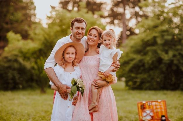 Familie van vierde twee mooie blonde dochters poseren in het park. zomer. ruimte kopiëren.