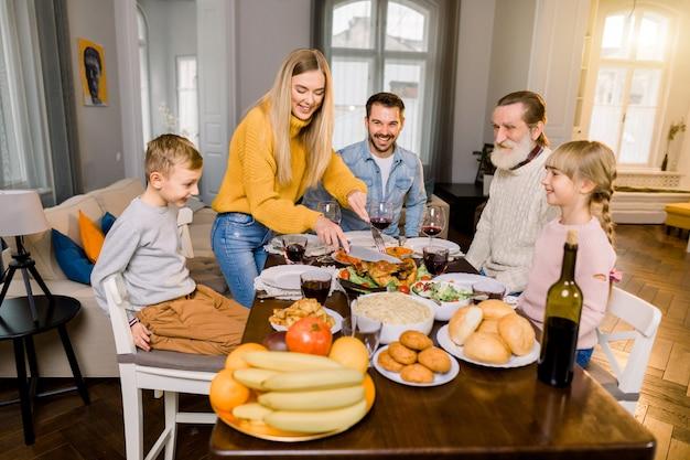 Familie van vijf mensen, grootvader, ouders en kinderen die aan tafel zitten en geroosterde kalkoen gaan eten, terwijl de gelukkige moeder turkije snijdt