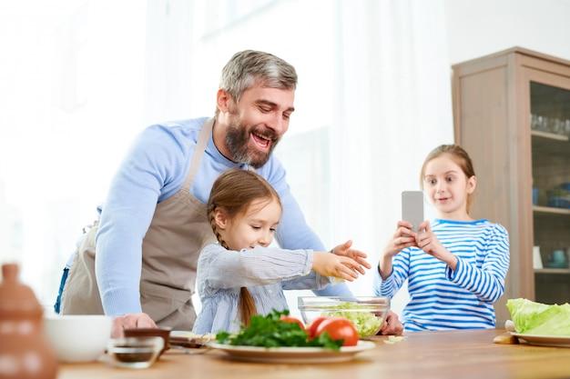Familie van voedselbloggers die salade voorbereiden