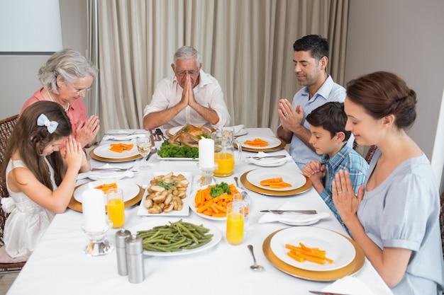 Familie van zes die gunst vóór maaltijd bij eettafel zeggen