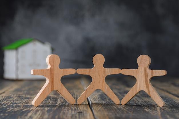 Familie veiligheidsconcept met houten figuren van mensen, model huis zijaanzicht.
