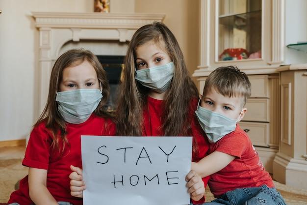 Familie verblijf thuis concept. drie kinderen in masker met bordje zeggen thuisblijven voor bescherming tegen virussen en zorgen voor hun gezondheid vanaf covid-19. quarantaine concept.