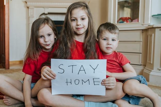 Familie verblijf thuis concept. drie kinderen met een bordje 'blijf thuis' voor bescherming tegen virussen en zorg voor hun gezondheid vanaf covid-19. quarantaine concept.