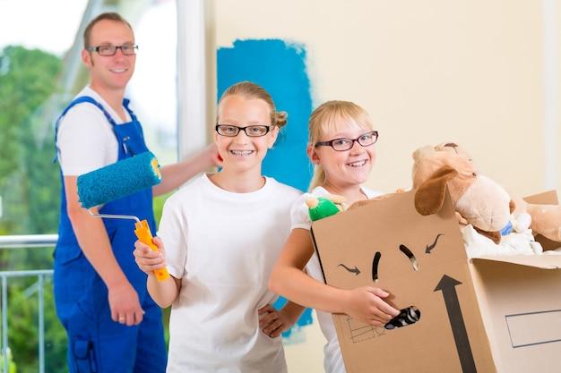 Familie verhuist met dozen vol spullen, ze schilderen de muren van hun nieuwe huis