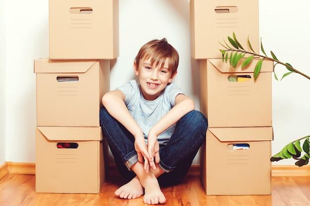 Familie verhuist naar een nieuw appartement. schattige jongen helpt bij het uitpakken van dozen.