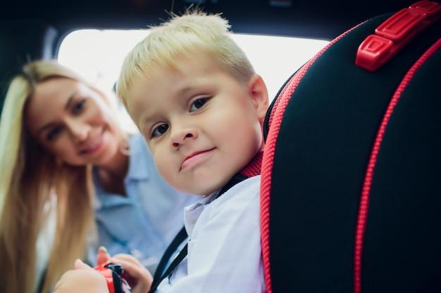 Familie, vervoer, wegreis en mensenconcept - gelukkig vrouwen vastmakend kind met veiligheidsgordel in auto