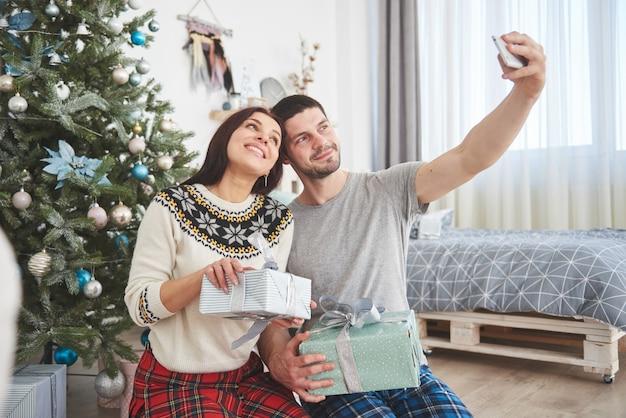 Familie verzameld rond een kerstboom, met behulp van een tablet