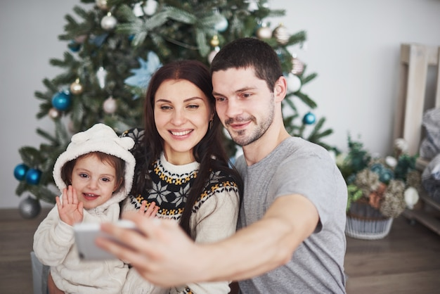 Familie verzamelde zich rond een kerstboom en maakte een selfie