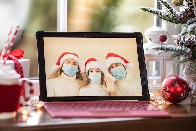 Familie viert kerstvakantie online door videochat in quarantaine. lockdown blijf thuis concept. kerstfeest tijdens pandemie coronavirus covid 19