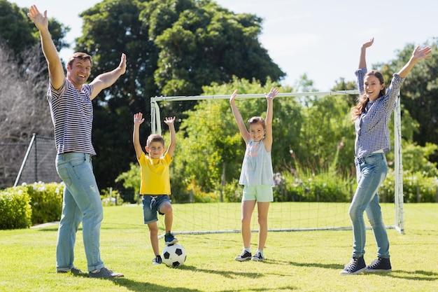 Familie voetballen samen in het park