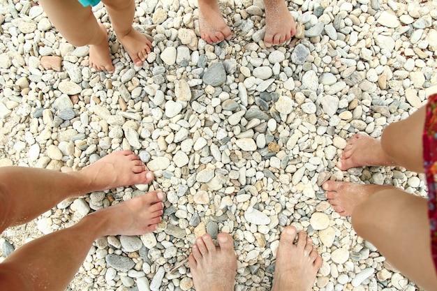 Familie voeten op het zand op het strand in de zomer