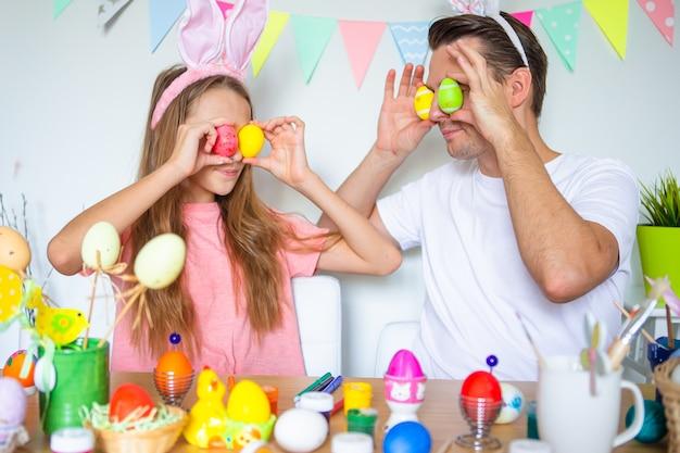 Familie voorbereiden op pasen en plezier maken. vader en zijn kleine dochter die konijntjesoren thuis dragen