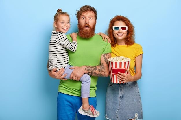 Familie, vrije tijd, entertainmentconcept. bange vader, lachende moeder en blije dochter kijken naar thriller of horrorfilm
