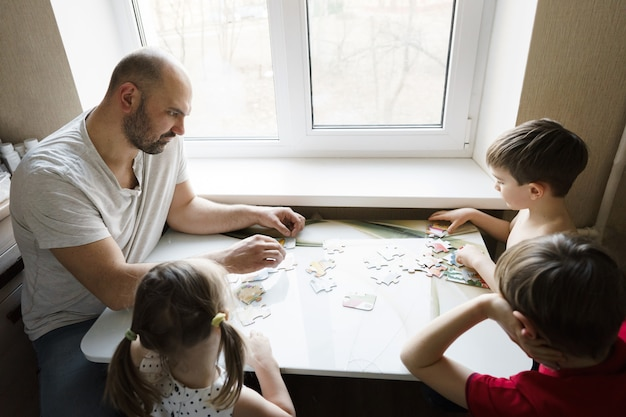 Familie vrije tijd: vader, zonen en dochter spelen samen bordspellen