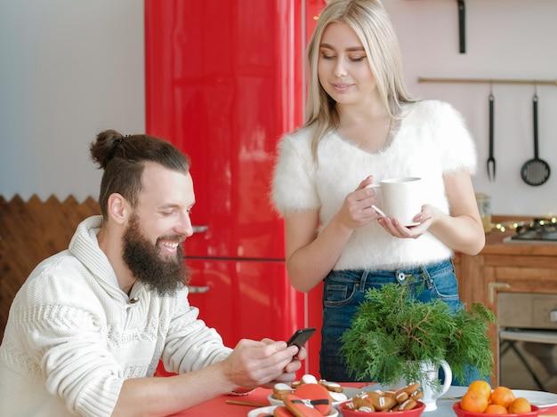 Familie vrijetijdsbesteding. echtpaar in moderne keuken. kerel zit aan feestelijke kersttafel, leuk nieuws lezen op smartphone.